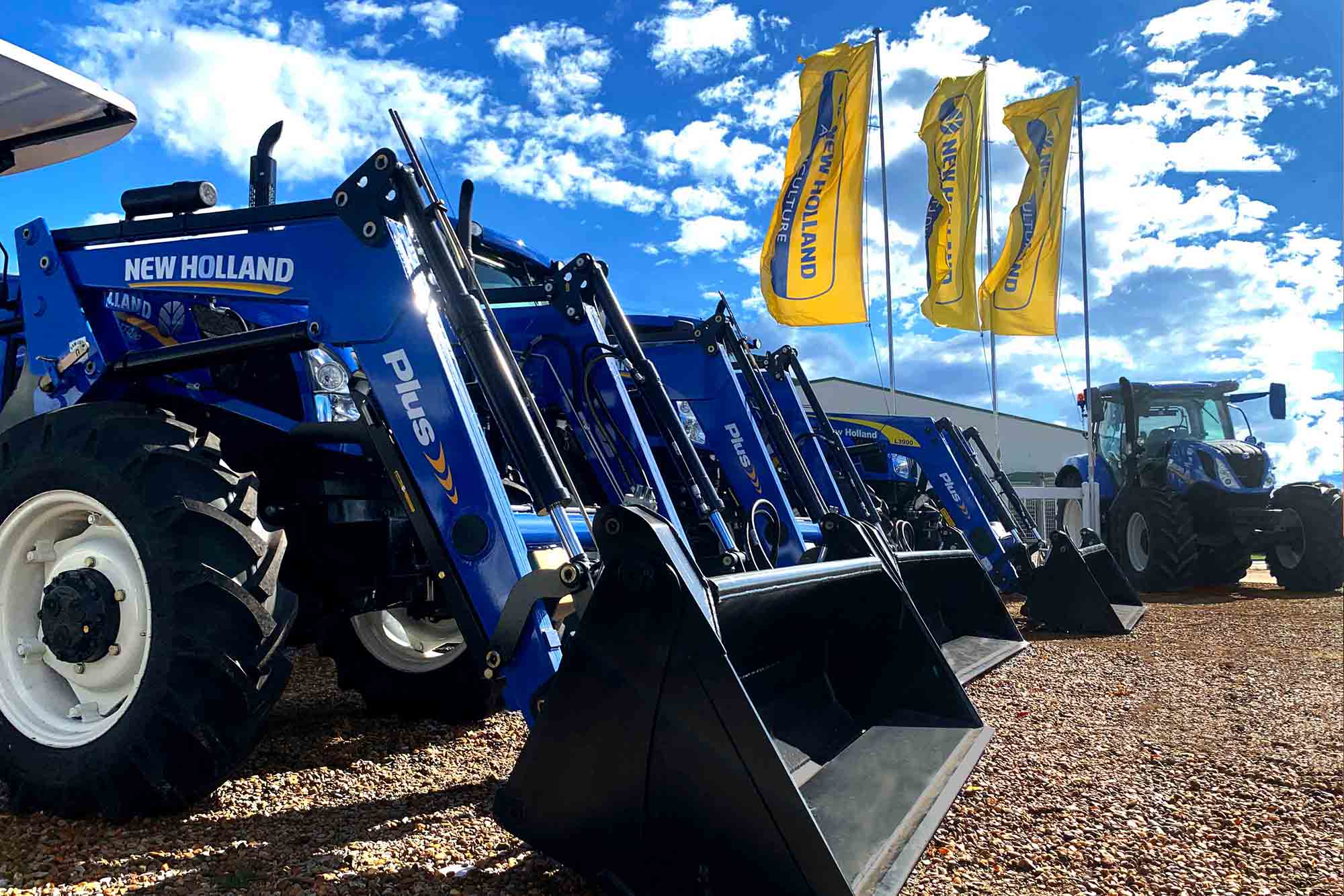 Line up of new holland tractors close up with flags flying in the sky